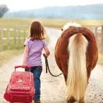 Ein Mädchen führt sein kleines Pony und zieht den Trolley aus der Sigikid-Serie Pony Sue hinterher. EIn schönes Foto.